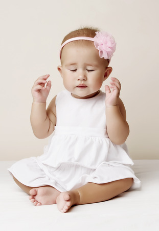 benevolence: Baby girl in white dress with flower