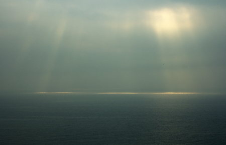 desolación: Sea horizon with ripples against grey sky at dusk bleakness over seascape background