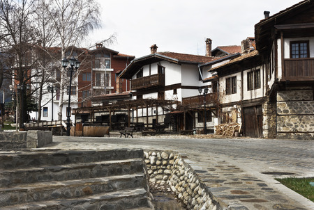 ethnographic: Bansko, Bulgaria - March 20, 2017: Old house stone paved road alley, wooden benches Bansko ski tourist centre of Bulgaria