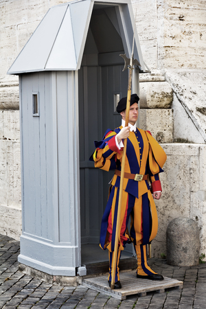 Rome, Vatican, Italy - April 14, 2017: Papal Swiss Guard in their traditional uniform stands at the entrance of Saint Peters Basilica Redakční