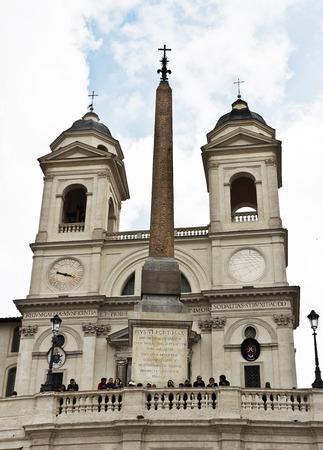 Rome, Italy - April 18, 2017: Trinita dei Monti, also Santissima Trinità al Monte Pincio - titular church (from April 13, 1587) in Rome, on top of the Spanish Steps.An antique obelisk (the Roman imitation of the Egyptian obelisk ) From the gardens of Sall