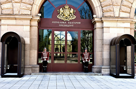 Sofia, Bulgaria - April 10, 2017:  Honor guards stand in front of the door to Presidents Office.The guards are dressed in a white and red dress uniform, which the royal guard wore back in the 19th century. Editorial