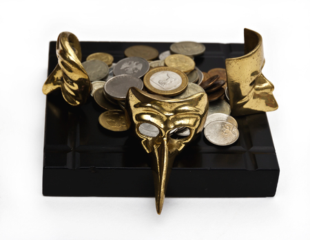 Beautiful carnival masks on a black countertop with coins