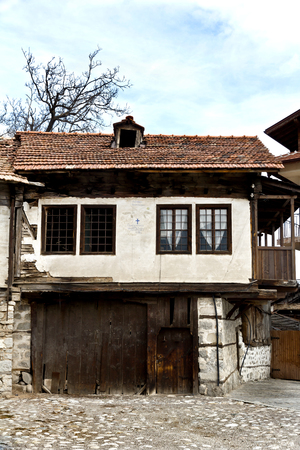 Old house stone paved road alley, wooden benches Bansko ski center of Bulgaria