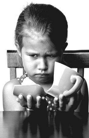 Frustrated little girl with a broken cup