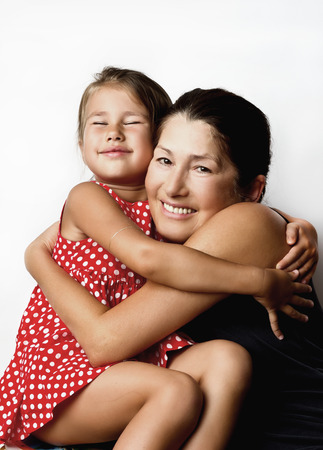 Affectionate grandmother and her cute little granddaughter smile at the camera Stock Photo