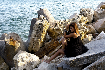 Cute girl posing on rocky boulders on the seashore