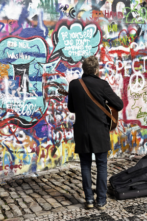 Prague, Czech Republic - March 30, 2018: Prague street musician songs at John Lennon wall