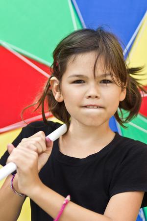 Beautiful little girl with big summer umbrella