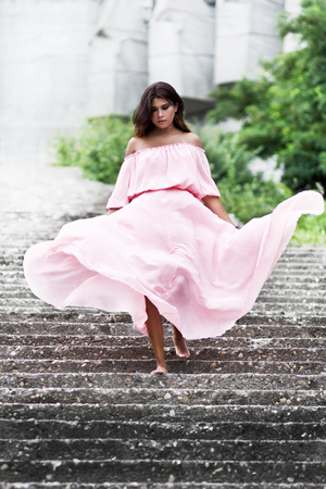Young woman in pink dress walking. Soft colors. Stockfoto