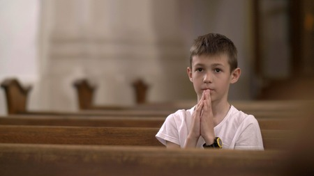 serious boy praying in the Church alone 스톡 콘텐츠