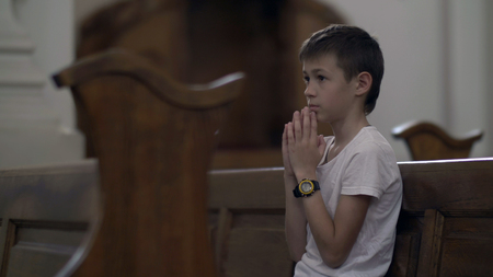 serious boy praying in the Church alone Stok Fotoğraf