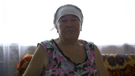 elderly woman with scarf on head at home