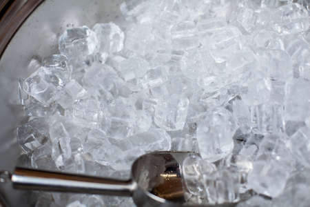 ice cubes in a bucket. ice shovel. Ice scoop on the ice cubes background, Top view with copy space and text.