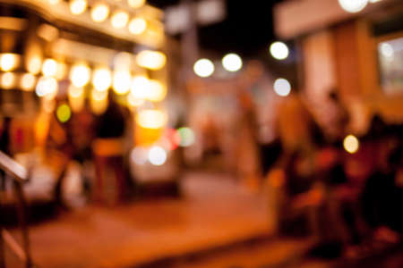 People rest in an ethnic, Mexican restaurant. Blurred photo. blur photo of restaurant with long table dinner and chair along it with bokeh light with yellow tone color