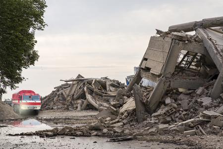Voiture de pompiers parmi les bâtiments en béton effondrés