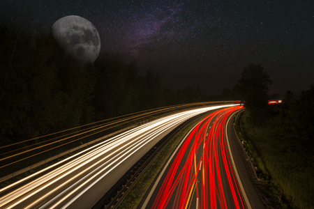 Trails on highway with stars and moon Stock Photo