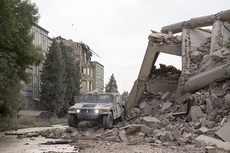 Military hummer in the middle of city ruins, collapsed houses