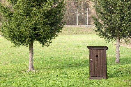 Earth closet, latrine next to spruces on a meadow . Waterless toilet.