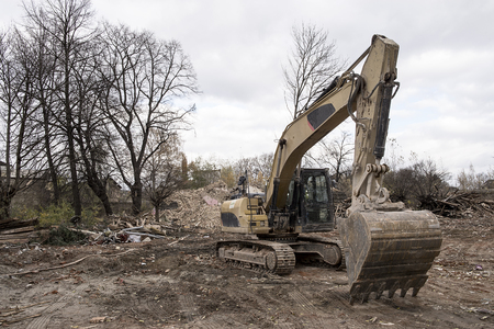 huge yellow shovel digger on demolition site Stock Photo