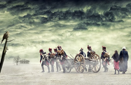 Napoleonic soldiers and women marching and pulling a cannon in plain land, countryside with stormy clouds. Soldiers going towards a damaged abonded house. Coming home. Stock Photo