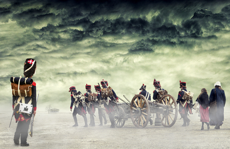 French grenadier watching napoleonic soldiers and women marching and pulling a cannon in plain land, countryside with stormy clouds. Soldiers going towards a damaged abonded house. Coming home.