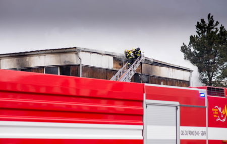 Prostejov Czech Rep 28th January - Firemen on a ladder by a roof fighting with fire in prefabricated house.