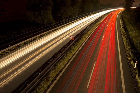 red and white light trails with a speed limit sign in the middle at night. Speed restriction 100km h