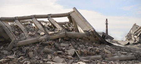 Industrial concrete building destructed by strike. Disaster scene full of debris, dust and crashed buildings. Imagens