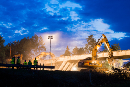 Olsany Czech Rep. 16th June 2018 Highway bridge demolition night scene. Hightway reconstruction site with reflectors, lights. Heavy excavators and diggers demolish a concrete bridge
