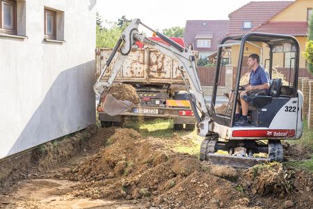 Prostejov Czechy 19.6.2018 Minikoparka na budowie. Koparka reguluje teren wokół domu. Koparka kopiąca ziemię i ładująca ją na samochód ciężarowy Publikacyjne
