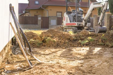 Mini escavatore in cantiere. L'escavatore regola il terreno intorno alla casa. Escavatore che scava il terreno con pale in primo piano Archivio Fotografico