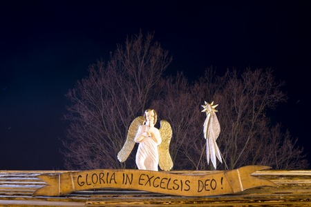 Night Christmas view on a wooden sculpture of an angle and comet star on wooden roof. Sign with reading Gloria in excelsis deo.