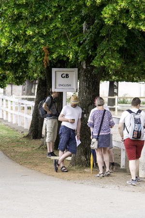 Lipica, Slovenia July 21st 2018. English tourists waiting by a sign of English language for a tour guide in Lipizzan stud farm. Tour Guide concept. Editorial