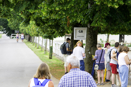 Lipica, Slovenia July 21st 2018. English tourists waiting by a sign of English language for a tour guide in Lipizzan stud farm. Tour Guide concept. 新闻类图片