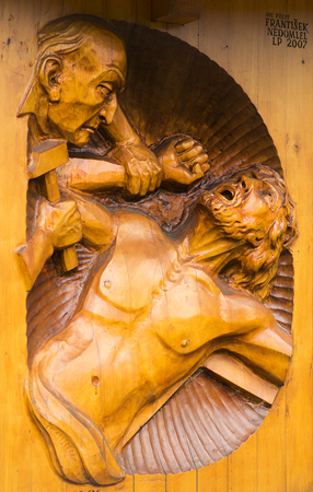 Bruntal Czechia, June 25 2014. Stations of the Cross. Number 11 Jesus is nailed to the cross. Wooden sculpture in dark brown wood from Mr Frantisek Nedomlel 新闻类图片