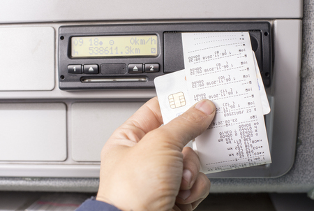Digital tachograph and drivers hand holding print with driving times of the day