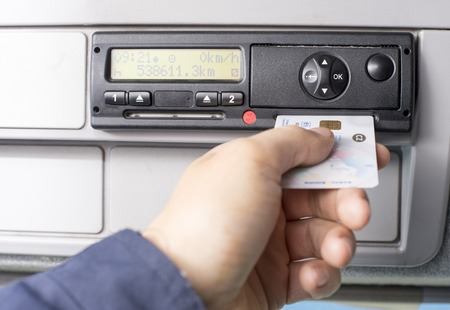 Digital tachograph and drivers hand inserting the digital card in the slot for the second driver