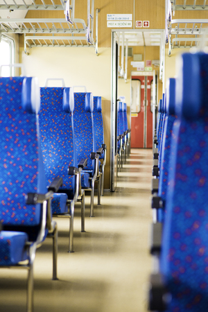 Image with the interior of a Czech train. An older train with comfortable and colorful chairs. - Image
