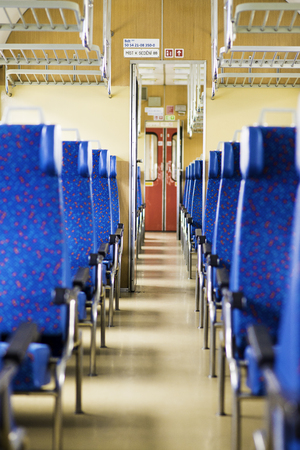 Image with the interior of a Czech train. An older train with comfortable and colorful chairs. - Image, Sign in background reads: Number of seats in the Czech language 免版税图像