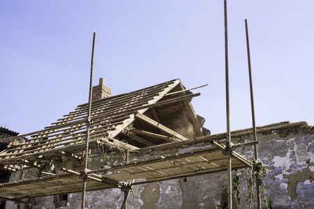 Litovel, Czech Republic August 3th 2018, scaffold standing by a clay house under reconstruction. Roof construction and timbers without tiles. Half of the roof blown away by the twind.