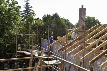 Litovel, Czech Republic August 3th 2018, a builder standing on scaffold by a clay house under reconstruction. Roof construction and timbers without tiles 新闻类图片