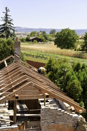 Litovel, Czech Republic August 3th 2018, top view on a carpenter standing on a roof timber construction of a clay house under reconstruction. Fields and mountains in background