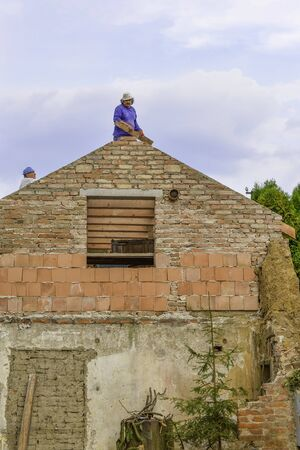 Litovel, Czech Republic August 3th 2018, Builder standing on a roof timber construction and finishing brick gable of an under reconstruction house. Blue cloudy sky above. View from bottom