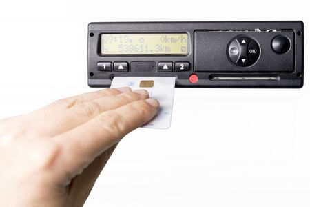 Digital tachograph and drivers hand inserting drivers card in it. No personal data. Isolated on white background