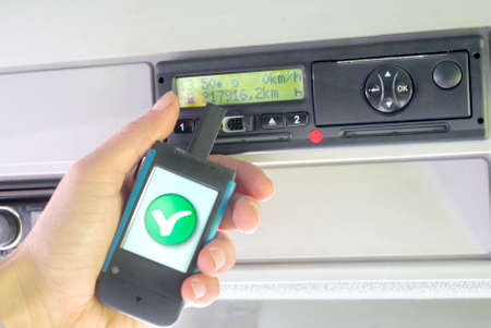 Digital tachograph and a hand holding a download key device. Digital tachograph driver card OK check. No personal data. 免版税图像