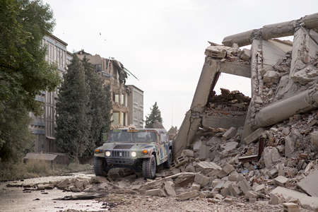 Military Humvee standing in the middle of collapsed concrete buildings
