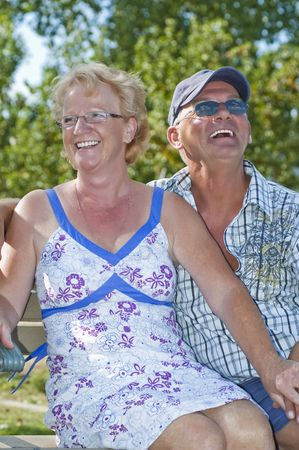 Aged couple sitting on a bench and laughing out loud Stock Photo - 4700124