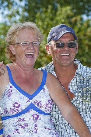 laughing out loud: Pareja ancianos sentados en un banco y re�rse a carcajadas Foto de archivo