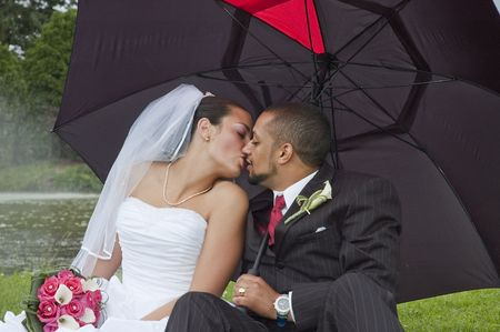 Just married multi ethnic couple kissing under an umbrella photo